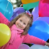 Liten flicka i rosa jacka står i hav av ballonger
