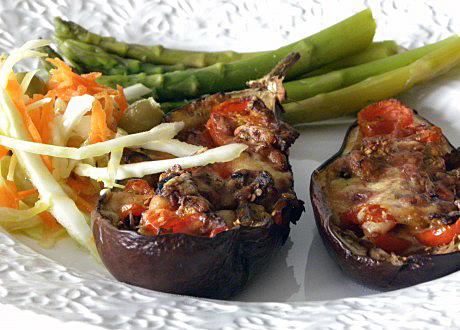 Fyllda auberginer med sparris, vitkål och morötter på vit tallrik