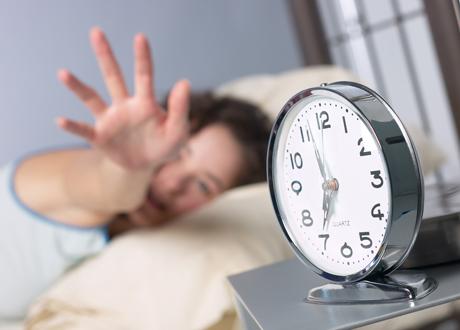 Ung kvinna i säng sträcker sig efter väckarklockan