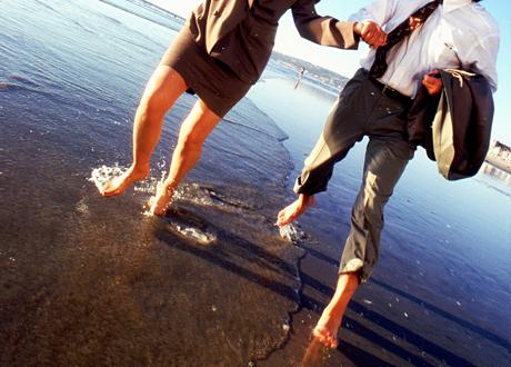 En man och en kvinna går med glada steg vid vattenbrynet inga ansikten syns