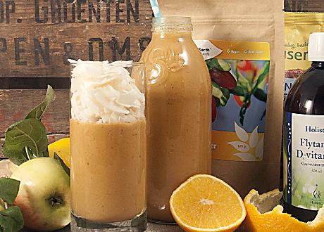 Smoothie i glas med apelsin och äpple bredvid snyggt upplägg