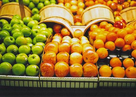 Äpplen och apelsiner på rad i butik