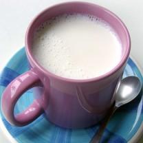 En lila mugg mjölk på blått fat med tesked