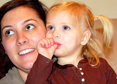 Mörkhårig mamma med sin ljushåriga tvååriga dotter som suger på tumme