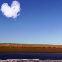 Himmel, moln, sjö och strand. Molnet ser ut som ett hjärta.