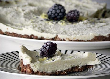 Raw cheesecake med citron på chokladbotten garnerad med frusna björnbär och rivet citronskal