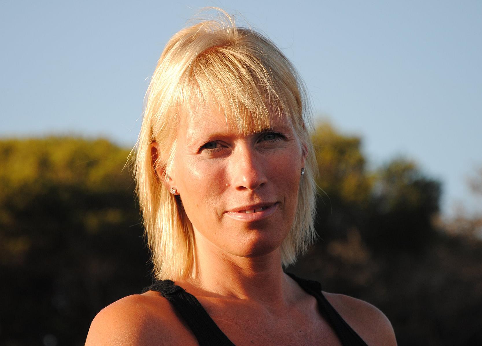 Blond snygg Malin Conradsen utomhus med linne och sol i ansiktet