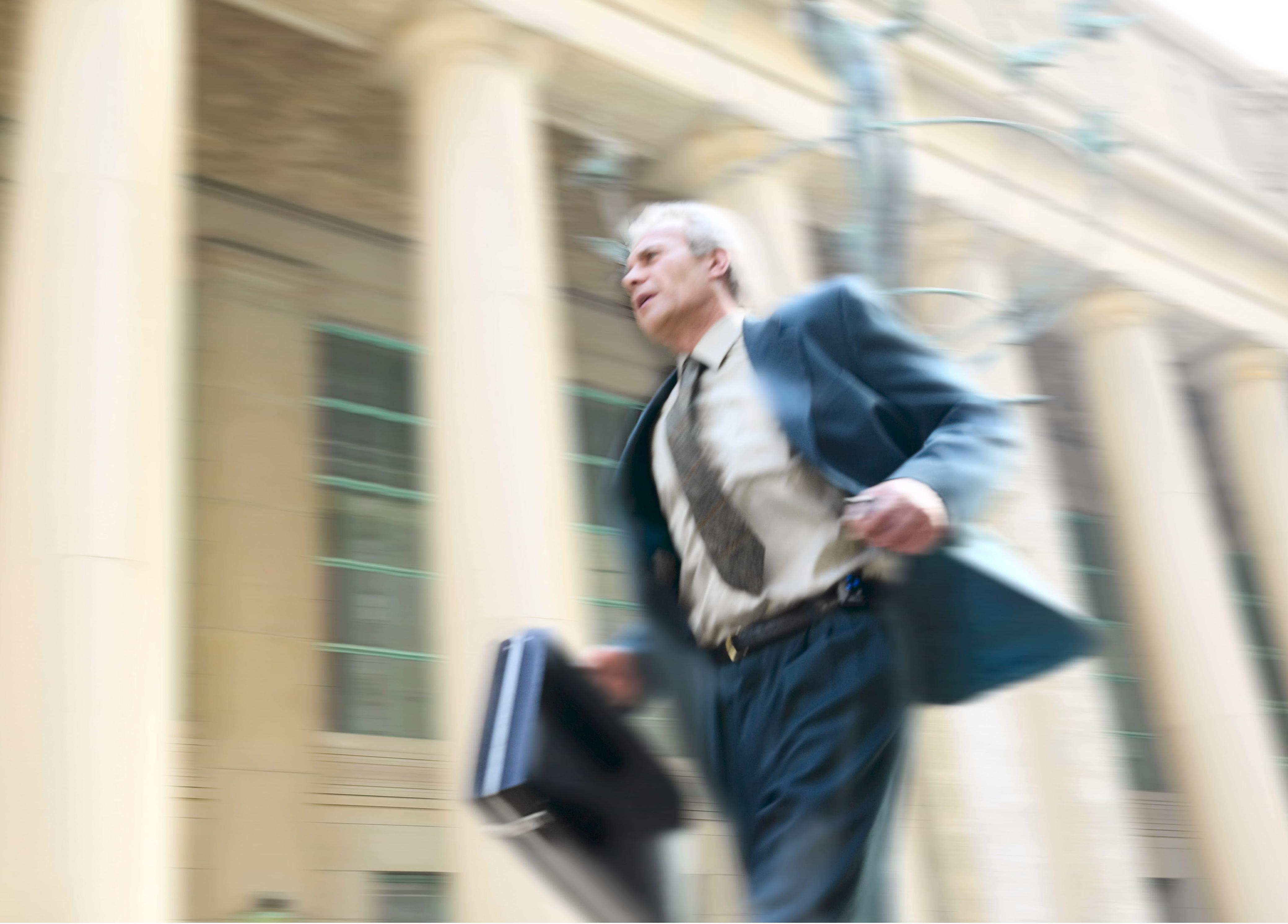 En äldre man i kostym springer stressad med en portfölj