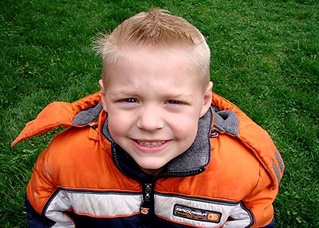 Fyråårig blond pojke i orange jacka tittar upp mot kameran ler lite stelt