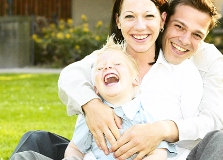 Leende familj bestående av mamma, pappa, femårig kille sitter på gräset
