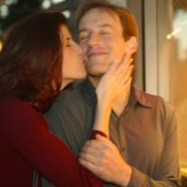 Kvinna kysser leende man på kinden