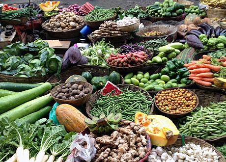 Korgar och dignande högar med grönsaker