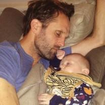 Pappa ligger och sover bredvid sin femmånaders bebis