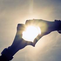 Två händer formar ett hjärta sol i bakgrunden