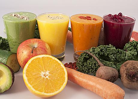 Fyra detox-smoothies samt frukt och grönsaker bredvid
