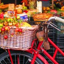 Cykel med cykelkorg full av grönsaker - intill frukt- och gröntstånd