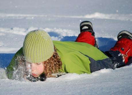 Lockhårigt barn med gröna vinterkläder och kängor ligger på mage i snön