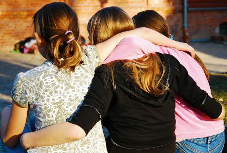 Tre tonårstjejer sitter och håller om varandra i eftermiddagssolen