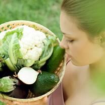 Kvinna tittar ner på korg med grönsaker