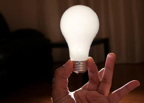 Hand håller upp en glödlampa