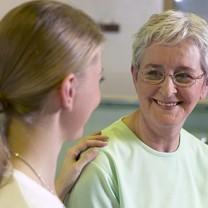 Yngre kvinna håller äldre kvinna på axeln