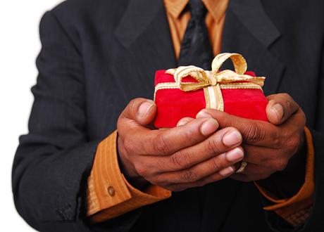 Mörka händer håller röd julklapp med guldband