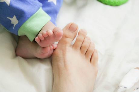 Bebisfötter bredvid mammas fot