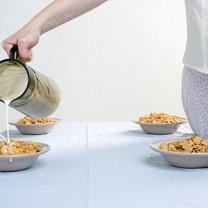 Kvinna häller mjölk i skålar