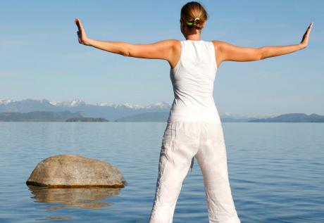kvinna i vitt gör yogapose vid vatten