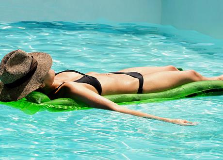 Ung kvinna solar på madrass i pool