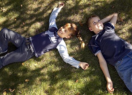 Tioårig tjej och kille ligger på gräset