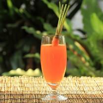 Glas med orange innehåll och en morot i står på bord