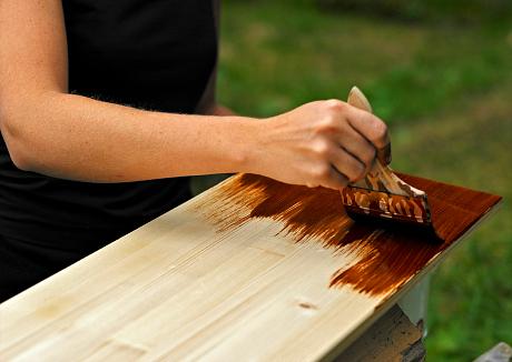 Kvinnohand håller en pensel mot en halvt brunmålad träplanka