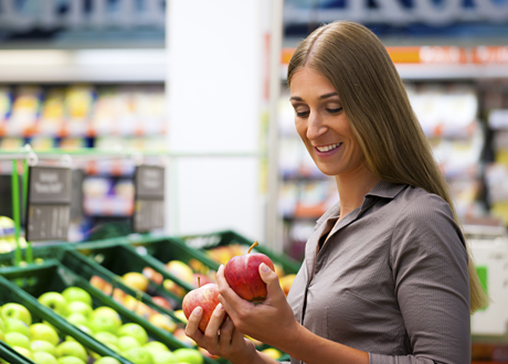 Kvinna i mataffär handlar äpplen
