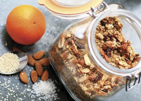 burk med granola, mandlar, riven kokos och en apelsin