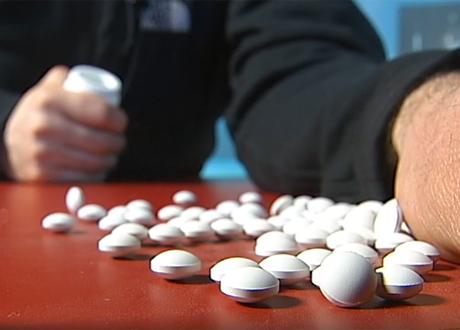 Hand håller i pillerburk piller syns på bord framför handen