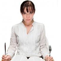 Kvinna sitter redo med kniv och gaffel