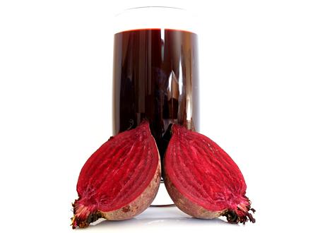 Glas med rödbetsjuice bredvid två rödbetshalvor