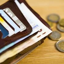 Plånbok med kort och sedlar, euro-mynt bredvid på bordet