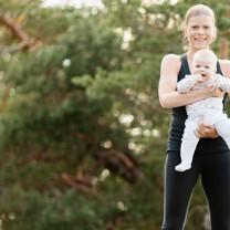 Terese Alvén i träningskläder håller i bebis