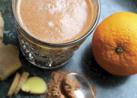 Glas med smoothie och en apelsin och superbärspulver