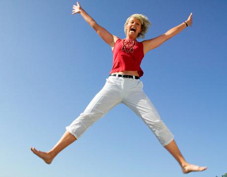 Kvinna hoppar blå himmel som bakgrund