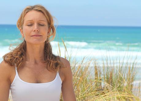 Kvinna sitter vid hav blundar och andas djupt