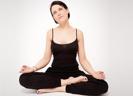 Mörkhårig kvinna sitter i yogaposition
