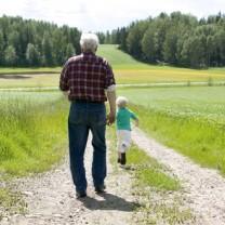 Äldre man går på landsväg med sonsonen springandes framför
