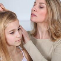 Mamma tittar i huvudet på dotter
