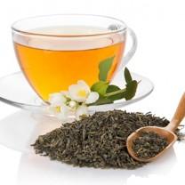 Glaskopp med grönt te blommor på fat och grönt te i lösvikt intill