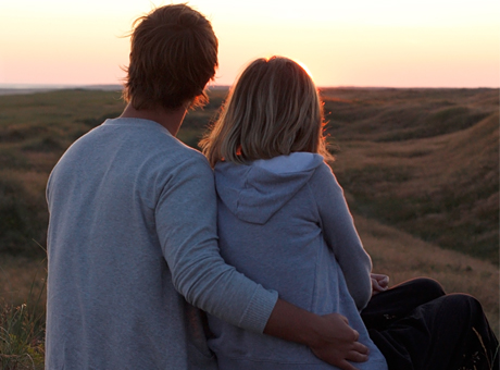Par håller om varandra i solnedgång