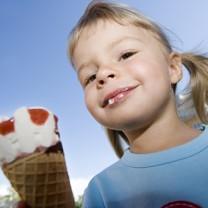 åttaårig flicka äter glass i strut