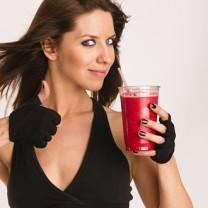 Mörkhårig tjej med röd smoothie gör tummen upp